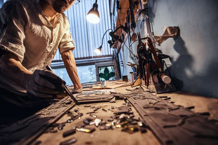 Diligent craftman is restoring ancient broken stained glass at his own workshop. 写真素材 - 124976007