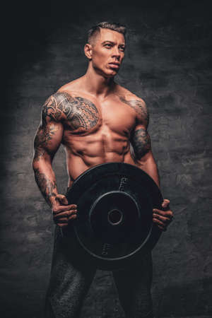 Shirtless muscular male with a tattoo on his chest holds barbell weights over grey background.