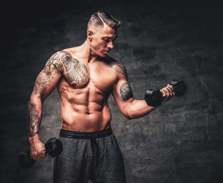 Athletic muscular shirtless male with tattoo on his chest doing biceps workouts with dumbbell. Foto de archivo