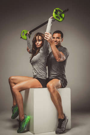 Attractive sporty male assisting sexy female in workouts with barbbel. Banco de Imagens