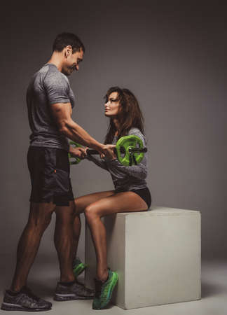 Middle age male coach assisting sexy woman with barbell workouts. 写真素材 - 124976073