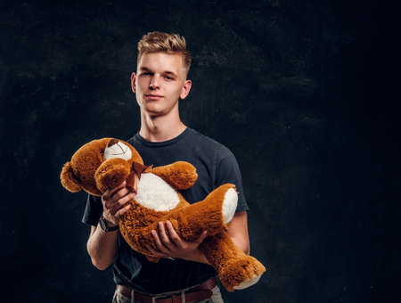 Pretty happy teenager posing with big plush bear over grey background at dark photostudio.