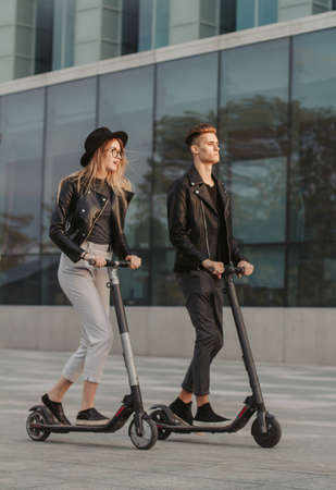 Young attractive couple on trendy scooters are riding in the city, near big glass building.