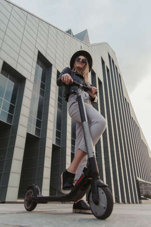 Attractive fashionable girl in sunglasses and hat is posing for photographer with her new scooter.