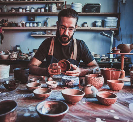 Pensive entusiastici potter in glasses at his own workshop is workig on a new handmade teapot.