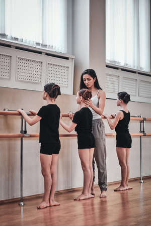 Cheerful talented trainer is showing to young girls how to do ballet exercises and correct them.