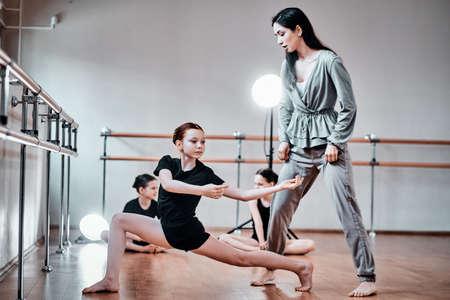 Three little girls have a rehearsal in training room with cheerful expirienced teacher. 版權商用圖片