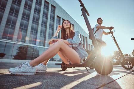 An einem hellen sonnigen Tag chillen ein paar junge Leute in der Nähe eines großen Gebäudes mit ihren Rollern. Foto mit niedrigem Winkel.