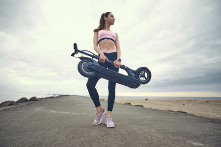 Low angle photo of pretty pensive girl with folded scooter in her hands. There are cloudy sky at background.