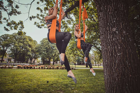 Two pensive beautiful womans are posing for photographer while resting on slings in the summer park.