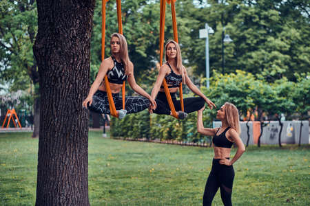 Two graceful pensive girls have training with their expirienced treiner on the slings in the green summer park. Stok Fotoğraf