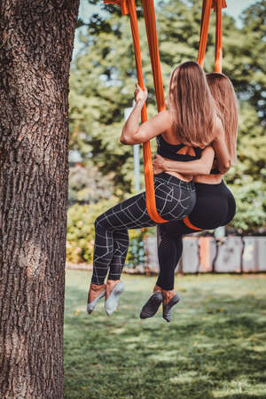 Couple of best friends are chilling on the orange slings under the tree in the summer park. Stok Fotoğraf