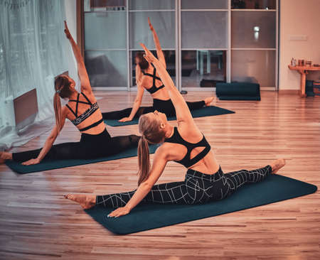 Private yoga class at bright airy studio with few girls, they are doing strechening.