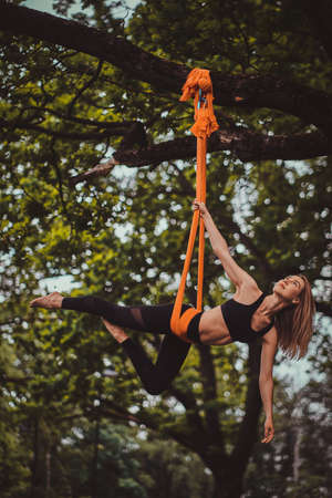 Beautiful pensive girl with long hair is doing exercises on sling in the summer forest. Stok Fotoğraf