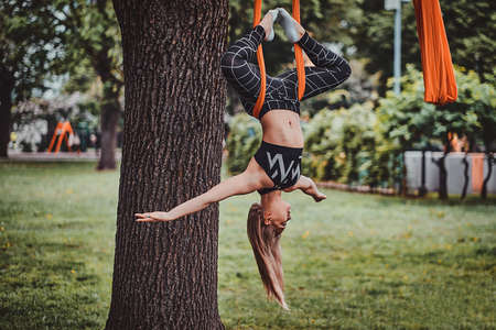 Young attractive woman with long hair is doing exercises on sling in the summer park.
