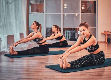Few young womens are enjoying joga classes at cozy studio. 版權商用圖片
