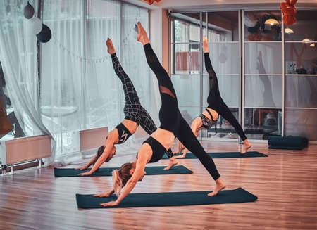 Weinig jonge vrouwen genieten van jogalessen in een gezellige studio.