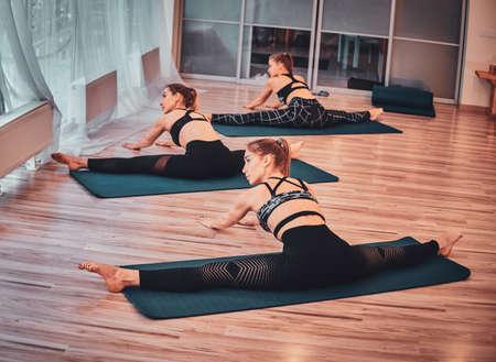 Thee pretty young womans are enjoying pilates at trendy gymnastic studio. 版權商用圖片