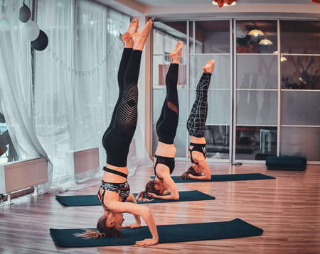 Three girls are standing together on the head at trendy yoga classes.
