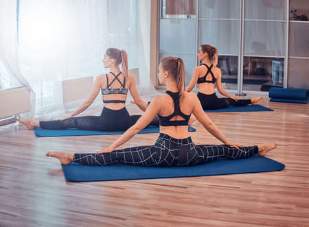 Group of attractive girls are practisaising yoga. They are siting in twine pose.