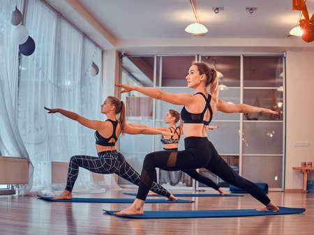 Process of yoga exercises with three beautiful young girls at gymnastic studio. 版權商用圖片