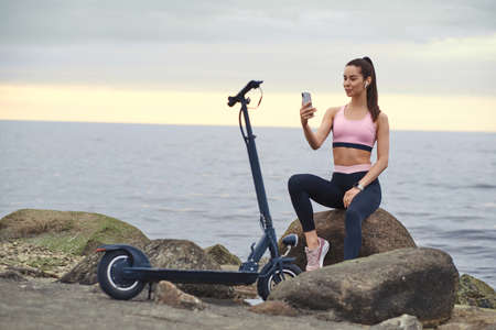 Young sportive woman is sitting on the stone with her electro scooter while chatting by mobile phone at seaside.