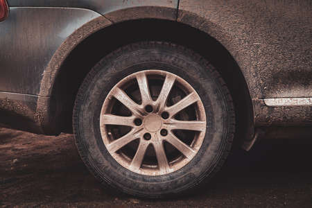 Closeup image of a dirty car after a trip around the countryside, focus on wheel. Stock Photo