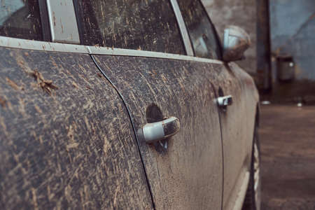 Closeup photo shoot of dirty cars door handles and window. Texture of mud on silver car.