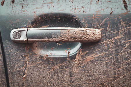 Closeup photo shoot of dirty cars door handle. Texture of mud on silver car. Stock Photo