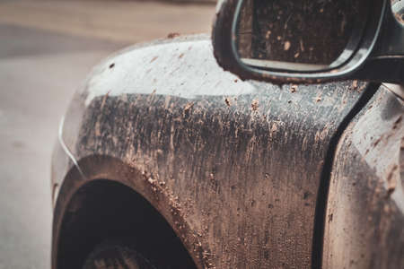 Closeup photo shoot of dirty cars mirror, splash and texture of mud on silver car. Stock Photo
