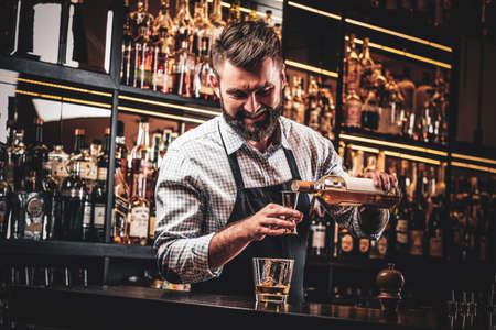 Diligent happy barman is preparing alcoholic beverage for customer.