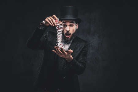 A Bearded magician in a black suit and top hat, showing trick with playing cards on a dark background.