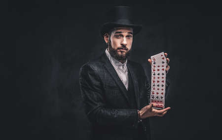 Magician showing trick with playing cards on a dark background. Stock fotó