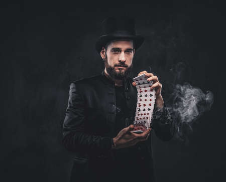 Magician in a black suit and top hat, showing trick with playing cards and magic smoke on a dark background. Stock fotó
