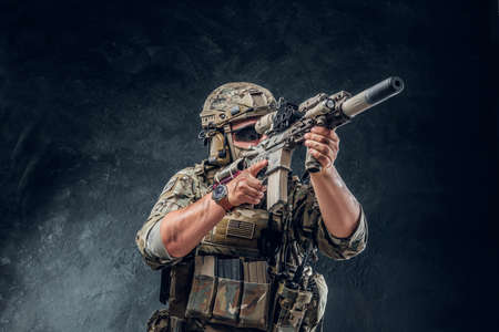 Military man in full equipment with wach on his hand is holding machine gun while posing for photographer over dark background.