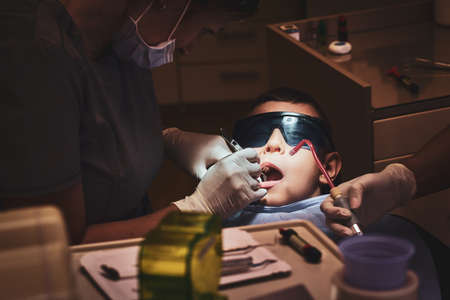 Brave small child gets a dental treatment by expirienced doctor at dental clinic.