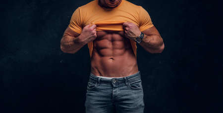 Sexual muscular bodybuilder is showing his well done sixpack at dark studio. Stock Photo