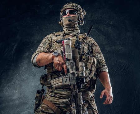 Odważny i silny wojskowy w masce i okularach przeciwsłonecznych trzyma karabin maszynowy. Zdjęcie Seryjne