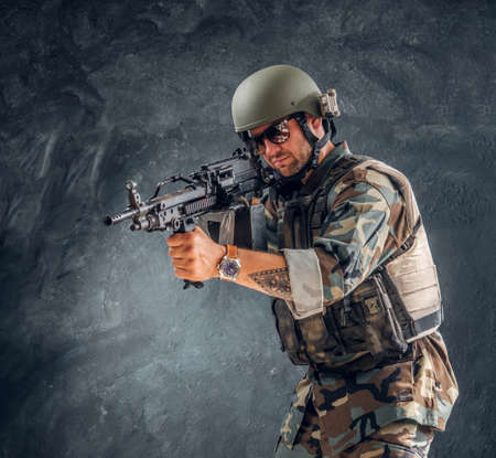 Męski przystojny wojskowy w kasku z tatuażem na ręce stoi na ciemnym tle, trzymając karabin maszynowy.