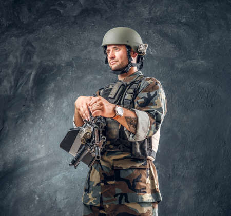 Manly handsome military man in helmet with tattoo on his hand is standing at dark background.