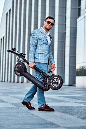 Happy smiling man is holding his new electro scooter in folded position while going to his office. Stockfoto