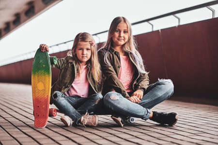 Two little cheerful sisters are sitting on the skateboard in the tunnel.