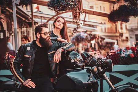 Beautiful couple with brutal biker and his sexy gilfriend are chilling near cefeteria with motorbike. Reklamní fotografie