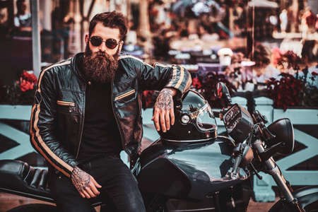 Handssome serious biker with beard and tattooes is sitting on his motorbike in busy city centre.