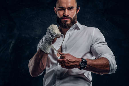 Bearded brutal man in white shirt is wearing protection on his fist before fight at dark studio.