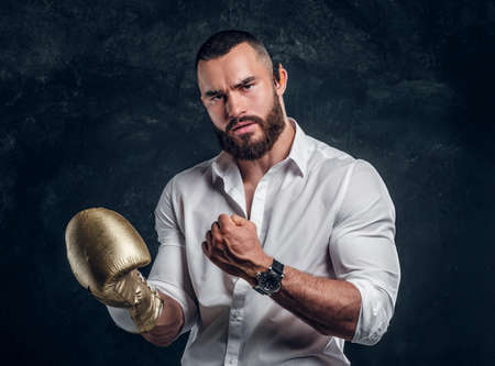 Angry serious man in white shirt is ready to fight while posing for photographer on the dark background.
