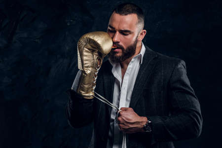 Handsome brutal man in protective boxing glove is vering mouth guard while posing for photographer.