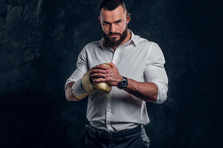 Cheeky handsome man in white shirt and with golden boxing glove is standing at dark studio.
