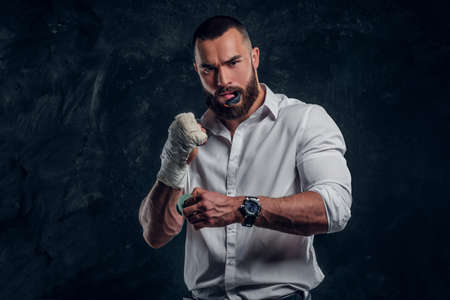 Attractive cheeky man in white shirt and mouth guard in his mouth is standing over dark background. Reklamní fotografie