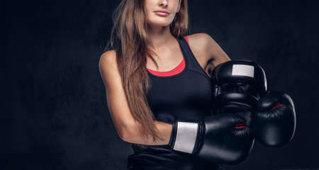 Attractive fit brunette is posing for photographer while holding helmet and wearig boxing gloves.
